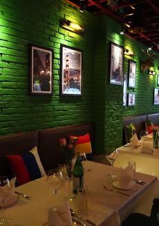 绿色的墙面上挂着许多艺术家画作